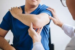 Doctor physiotherapist assisting a male patient while giving exercising treatment massaging the arm of patient in a physio room, rehabilitation physiotherapy concept